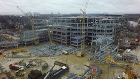 An aerial view of a busy construction site filled with cranes, building frames and metal beams. An aerial view of a busy construction site on a dirty puddly stock video