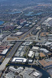 Aerial view of busy highway road. Busy freeway flowing through an urban city and suburban areas as seen from a plane Stock Photos