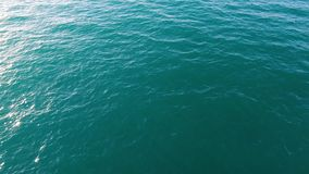 Aerial view of calm sea or ocean water surface, natural background. Stock. Top view of clean ocean water with sunflares. royalty free stock photos
