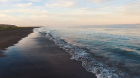 Aerial view. The camera flies straight to the sea. Sun at sunset shining into the camera.  stock footage