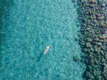 Aerial view of a canoe in the water floating on a transparent sea. Bathers at sea. Zambrone, Calabria, Italy. Diving relaxation and summer vacations. Italian stock photo
