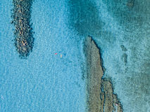 Aerial view of a canoe in the water floating on a transparent sea. Bathers at sea. Zambrone, Calabria, Italy. Diving relaxation and summer vacations. Italian stock image