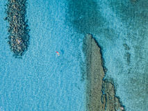 Aerial view of a canoe in the water floating on a transparent sea. Bathers at sea. Zambrone, Calabria, Italy. Diving relaxation and summer vacations. Italian stock photography