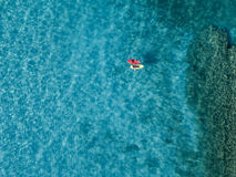 Aerial view of a canoe in the water floating on a transparent sea. Bathers at sea. Zambrone, Calabria, Italy. Diving relaxation and summer vacations. Italian royalty free stock photography