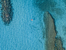 Aerial view of a canoe in the water floating on a transparent sea. Bathers at sea. Zambrone, Calabria, Italy Royalty Free Stock Photography