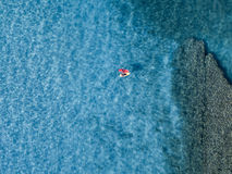 Aerial view of a canoe in the water floating on a transparent sea. Bathers at sea. Zambrone, Calabria, Italy Stock Photos