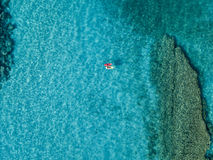 Aerial view of a canoe in the water floating on a transparent sea. Bathers at sea. Zambrone, Calabria, Italy Stock Images