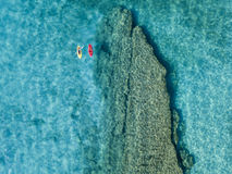 Aerial view of a canoe in the water floating on a transparent sea. Bathers at sea. Zambrone, Calabria, Italy Royalty Free Stock Image