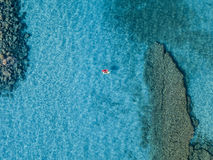 Aerial view of a canoe in the water floating on a transparent sea. Bathers at sea. Zambrone, Calabria, Italy. Diving relaxation and summer vacations. Italian stock images