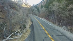 Aerial view of a canyon road with a car driving by the forested area stock footage