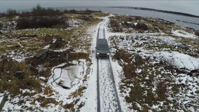 Aerial view of car driving away from shore in winter stock video footage