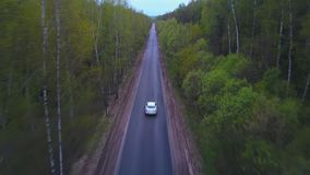 Follow view from drone above white premium car riding on lonely road. Aerial view car driving on countryside road among summer forest. Follow view from drone stock footage