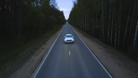 Aerial view car driving on dark countryside road among summer forest at evening. Front view from drone above car with headlights riding on night village road stock video footage