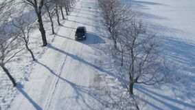 Aerial view of a car driving on the empty snowy road. stock video
