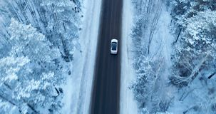 Aerial view on a car driving on winter country road in snowy forest. stock footage