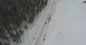 Aerial view of car driving among the winter forest covered with snow. Car driving on winter country road in snowy forest. Aerial footage stock video footage