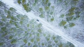 Aerial view on car driving through winter forest road. Scenic wi. View from height on car driving through winter forest road. Scenic winter landscape Stock Photo