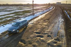 Aerial view of car moving along muddy rural road in bad condition on sunny spring or winter day.  royalty free stock image