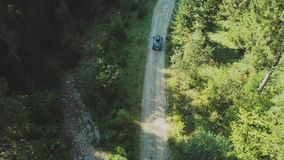 Aerial view of car riding on the road in the coniferous forest among the mountains. Road trip at summer in Romania.