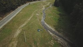 Aerial view of car riding on the road in the coniferous forest among the mountains. Tourists take selfie near car in the