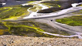 Aerial view of a car running at the beautiful mountain and the stream at Lanmannalaugar stock video