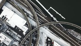 Aerial view car traffic on city highway next to snowy railroad and riverside boat dock. This is a top down aerial view of snowy city highway traffic. Cars and stock video footage