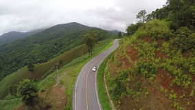 Aerial View - Car on a winding road in the hills. Thailand. stock footage
