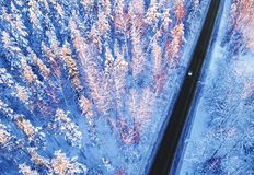 Aerial view of a car on winter road in the forest. Winter landscape countryside. Aerial photography of snowy forest with a car on stock images