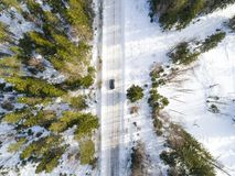 Aerial view of a car on winter road. Winter landscape countryside. Aerial photography of snowy forest with a car on the road. Stock Images