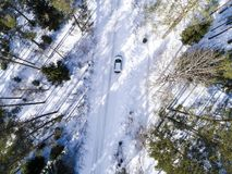 Aerial view of a car on winter road. Winter landscape countryside. Aerial photography of snowy forest with a car on the road. Stock Image