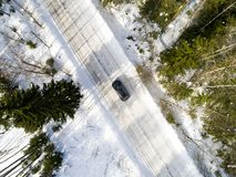 Aerial view of a car on winter road. Winter landscape countryside. Aerial photography of snowy forest with a car on the road. Royalty Free Stock Photography