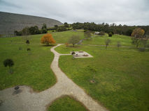 Aerial view of Cardinia Reservoir Park, Melbourne, Australia. Aerial view of Cardinia Reservoir Park - grassy area, walking path, bare trees, and forest Stock Image