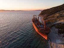 Aerial view of cargo ship run aground on wild coast, shipwreck after storm. Drone shot stock photo