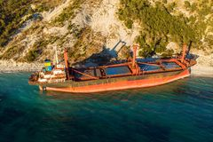Aerial view of cargo ship run aground on wild coast, shipwreck after storm. Drone shot royalty free stock photography