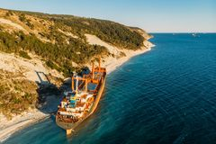 Aerial view of cargo ship run aground on wild coast, shipwreck after storm. Drone shot stock photos