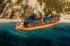 Aerial view of cargo ship run aground on wild coast, shipwreck after storm. Drone shot stock image