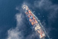 Aerial view of a cargo ship at sea. Partly covered with clouds Royalty Free Stock Photo