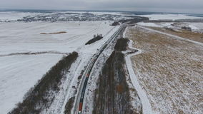 Aerial view of cargo train delivering goods, fuel, petroleum in winter. 4K stock video footage
