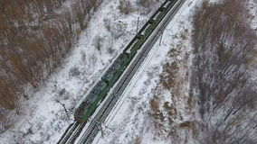Aerial view of cargo train delivering goods, fuel, petroleum in winter. stock video