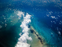 Aerial view of Caribbean island chain. CARIBBEAN: Aerial view of clouds and the beautiful turquoise waters surrounding a chain of islands in the Caribbean stock images