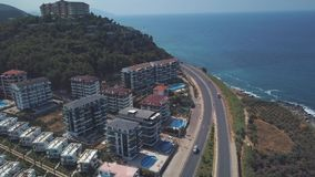 Aerial view of cars moving in the road near the sea and luxury hotels standing on the slope in warm summer day. Clip stock video