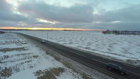 Aerial view of cars moving on winter road. Amazing sunset. Nature winter landscape. Aerial footage stock video
