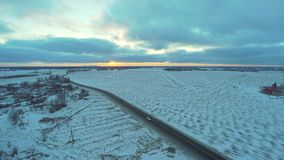 Aerial view of cars moving on winter road. Amazing sunset. Nature winter landscape. Aerial footage stock footage