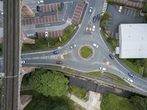 Aerial view of cars on a roundabout. Top view of cars on vehicles on a mini roundabout by a viaduct and industrial buildings. Elevated drone photography Royalty Free Stock Photo