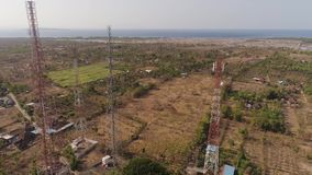Cell phone towers. Aerial view cell phone towers line in Bali, Indonesia. Telecommunication tower, communication antenna on coast sea stock footage