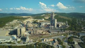 Aerial view of cement factory, large industrial building in the mountains. Concept of cisterns, pipes, metal structures. Concrete production. Daytime footage stock video footage