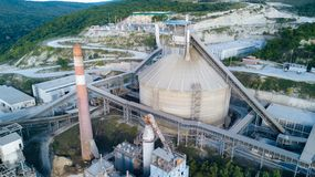 Aerial view of cement manufacturing plant. Concept of buildings at the factory, steel pipes, giants. Aerial view of cement manufacturing plant. Concept of stock images