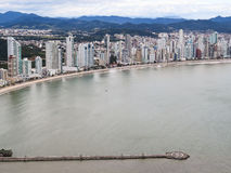 Aerial view of city with buildings by the sea. Panoramic view on sunny city day with buildings by the sea and green ocean Royalty Free Stock Image