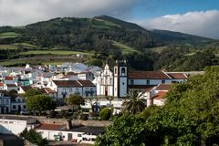 Agua de Pau, Sao Miguel, Azores Islands. Aerial view on the city, with its white houses and a church built in traditional portuguese style. Mountains and a royalty free stock photo
