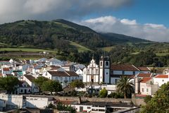 Agua de Pau, Sao Miguel, Azores Islands. Aerial view on the city, with its white houses and a church built in traditional portuguese style. Mountains and a stock photography